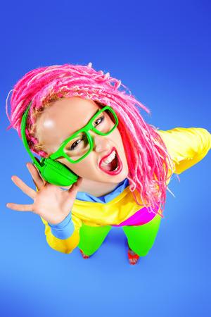 gente loca: Loco expresiva chica DJ de moda en ropa brillante, auriculares y rastas brillantes. Disco, fiesta. Bright fashion. Foto de archivo