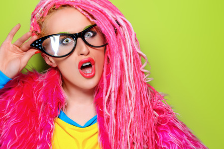 original: Modern pin-up girl in bright clothes and pink dreadlocks. Disco, party. Bright fashion.