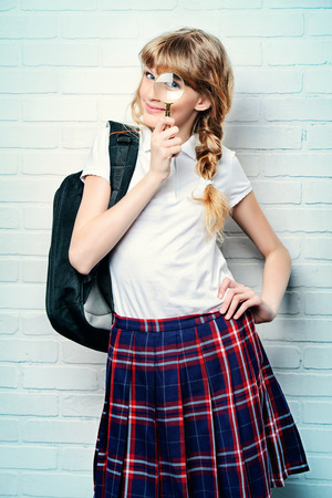 checkered skirt: Cute teen girl in school uniform looking through a magnifying glass. Education. Studio shot. Stock Photo