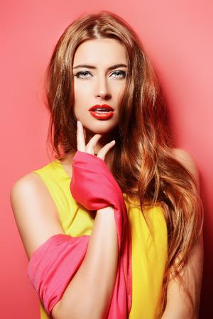 moda ropa: Retrato de la belleza de una mujer joven sensual en brillante pañuelo carmesí sobre fondo rosa. Belleza, la moda. Cosméticos.