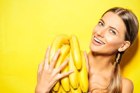 comiendo platano: Mujer joven hermosa con los pl�tanos. Frutas tropicales. Concepto del verano. Alimentaci�n saludable.