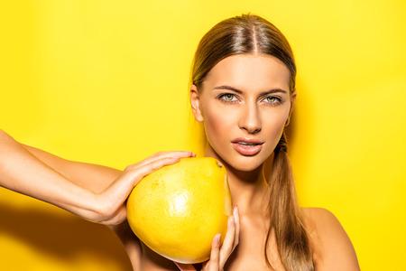 frutas tropicales: Mujer joven natural que sostiene el pomelo sobre fondo amarillo. Frutas tropicales. Concepto del verano. Alimentación saludable. Foto de archivo