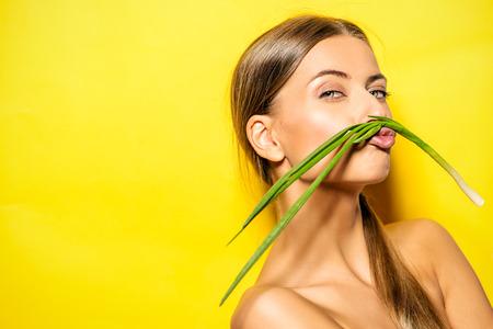 cebolla: Mujer joven alegre con la cebolla verde sobre fondo de verano amarillo. Comida saludable.