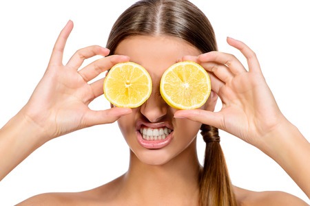 Funny laughing woman holding two juicy lemons before her eyes. Healthy eating concept. Diet. Isolated over white.