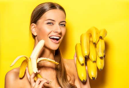 niña comiendo: Mujer joven hermosa con los plátanos. Frutas tropicales. Concepto del verano. Alimentación saludable.