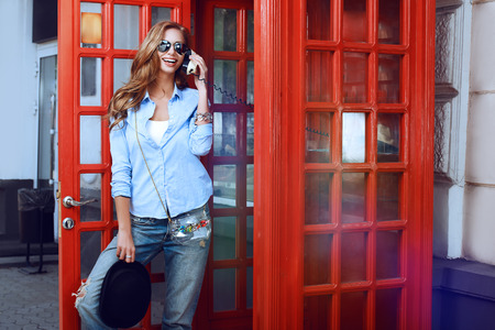telephone booth: Pretty young woman talking on the phone in telephone booth. Europe, England. Vacation, tourist trip.