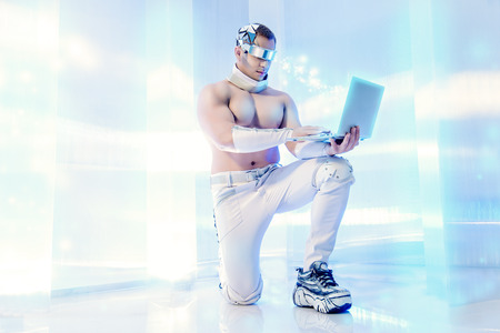 cyber business: Handsome muscular man of the future wearing futuristic glasses working on a laptop. Technologies of the future. Stock Photo