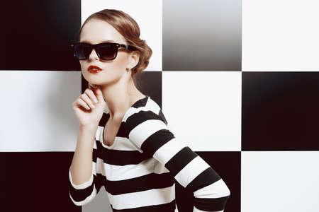 rayas: Hermosa modelo posando en traje de rayas blancas y negras sobre un fondo de cuadrados blancos y negros. Belleza, concepto de moda. El estilo de negocios.