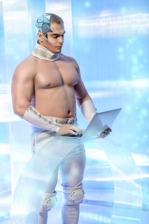 futuristic man: Handsome muscular man of the future wearing futuristic glasses working on a laptop. Technologies of the future. Stock Photo