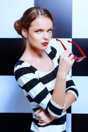 Beleza: Forme o tiro de um modelo elegante nos vidros que levanta no vestido de listras pretas e brancas em um fundo de quadrados pretos e brancos. Beleza, conceito da forma. Estilo do neg