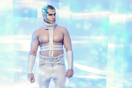futuristic man: Futuristic handsome man with perfect muscular body stands on a luminous transparent background. Technology. Future concept. Stock Photo
