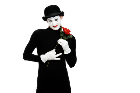 Emotional male mime artist with red rose performing love. Isolated over white. Stock Photo