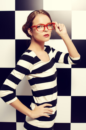 glasses model: Fashion shot of an elegant model in glasses posing in dress in black and white stripes on a background of black and white squares. Beauty, fashion concept. Business style. Stock Photo