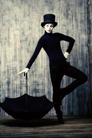 pantomima: Elegante mimo masculino en sombrero de copa presenta con el paraguas por un muro de grunge.