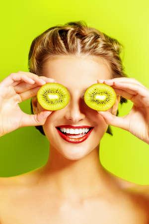 cosmeticos: Mujer joven alegre celebración de kiwi delante de sus ojos. Fondo verde. Frutas tropicales. Alimentación saludable. Belleza, cosméticos. Foto de archivo