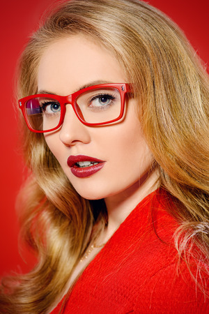 eyewear fashion: Beautiful young woman with magnificent blonde hair wearing red dress and elegant red glasses. Beauty, fashion. Optics, eyewear. Red background.