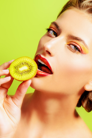 sexy food: Beautiful sexy young woman eating kiwi over green background. Tropical fruits. Healthy eating. Beauty, cosmetics.