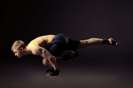 acrobat gymnast: Handsome muscular male athlete performs gymnastic exercise. Sports, acrobatics, gymnastics.