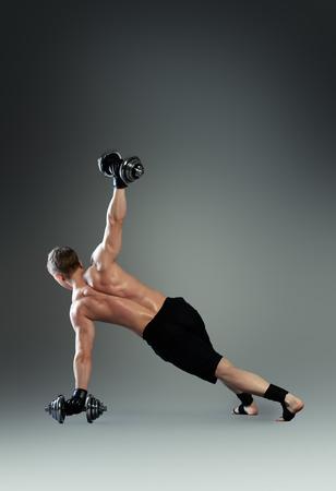 acrobacia: Hermoso atleta masculino muscular realiza ejercicio gimnástico. Deportes, la acrobacia, la gimnasia. Foto de archivo