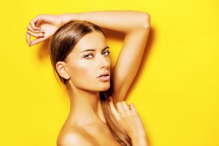 nude young: Чувственный молодая женщина с естественным макияж, создавая на фоне ярко-желтый. Скопируйте пространства. Косметика. Уход за кожей, уходу за телом.