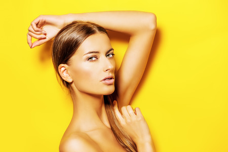 young naked girl: Sensual young woman with natural make-up posing over bright yellow background. Copy space. Cosmetics. Skincare, bodycare.