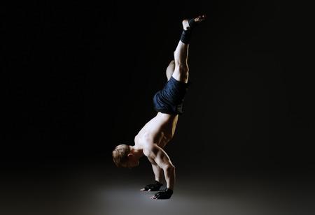 acrobatics: Hermoso atleta masculino muscular realiza ejercicio gimn�stico. Deportes, la acrobacia, la gimnasia. Foto de archivo