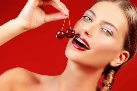 juicy: Attractive young woman eating fresh cherry. Sexual lips, red lipstick. Healthy food concept. Cosmetics. Red background. Stock Photo