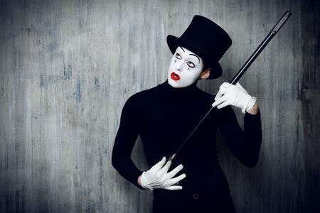 mimo: Elegante mimo masculina expresiva posando con el bast�n por una pared del grunge. Foto de archivo