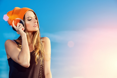 escucha activa: Mujer joven moderna escuchar m�sica en los auriculares al aire libre