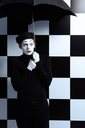 dramatic characters: Portrait of a male mime artist standing under umbrella expressing sadness and loneliness