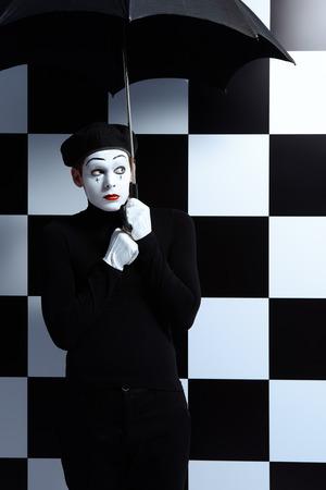 mimo: Retrato de un mimo sexo masculino se coloca bajo el paraguas de expresar la tristeza y la soledad Foto de archivo