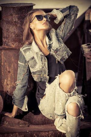 mezclilla: Mujer joven imponente en ropa de jeans posando sobre fondo urbano Foto de archivo