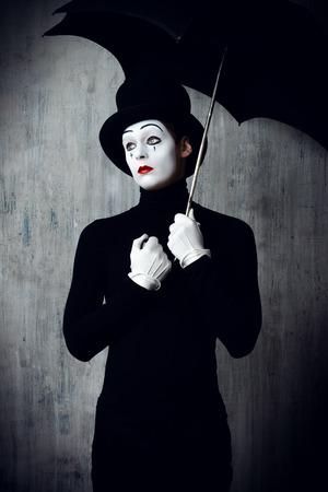 pantomima: Retrato de un mimo sexo masculino se coloca bajo el paraguas de expresar la tristeza y la soledad Foto de archivo