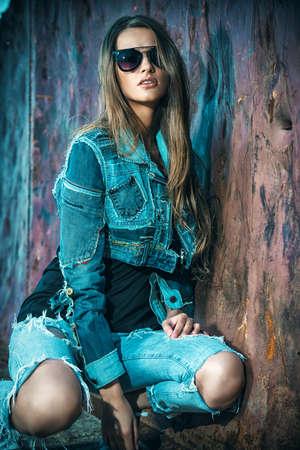 in jeans: Mujer joven imponente en ropa de jeans posando sobre fondo urbano. Foto de archivo