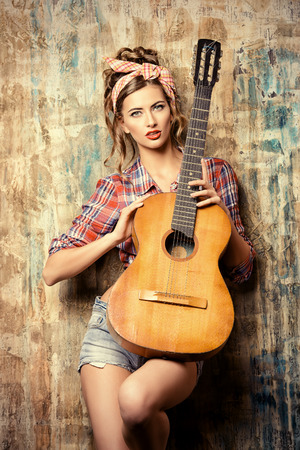 fashion girl style: Pretty pin-up girl posing with guitar Stock Photo