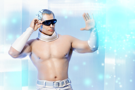 futurism: Handsome muscular man with futuristic make-up wearing glasses stands on a luminous transparent background and touches something virtual. Stock Photo