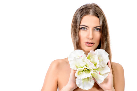 Tender young woman with clean fresh skin posing with white flower
