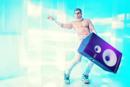 futuristic man: Futuristic muscular man dancing with huge music speakers on a luminous transparent background