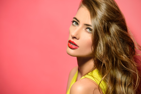 woman hairstyle: Fashion model in bright yellow dress posing over pink background Stock Photo
