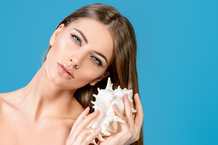 seashell: Beautiful young woman with clean fresh skin posing with seashell