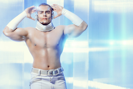 futuristic man: Handsome muscular man with futuristic make-up in the headphones standing on a luminous transparent background.