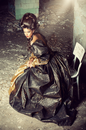 updo: Art Fashion. Beautiful young woman in elegant historical dress and with barocco updo hairstyle posing in the ruins of the castle. Renaissance. Barocco.
