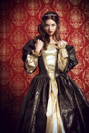 se�ora mayor: Se�ora joven hermosa en el vestido caro exuberante que presenta sobre el fondo de la vendimia. Renacimiento. Barocco. Moda.