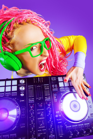 modern generation: Expressive modern DJ girl wearing bright clothes, headphones and bright dreadlocks mixing up some music. Disco, party. Modern generation.