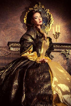 se�ora mayor: Estilo Renacimiento - hermosa mujer joven en el vestido caro exuberante en un antiguo palacio interior. Estilo vintage. Moda.