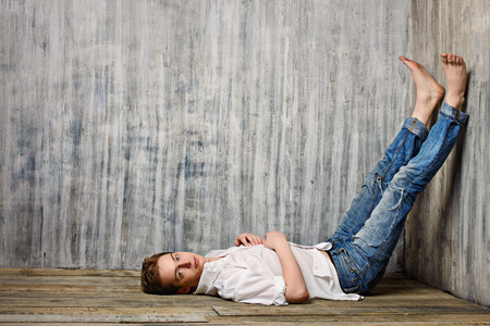 barefoot man: Romantic young man lying on the wooden floor by a grunge wall.
