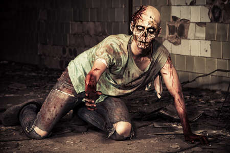 evil: Horrible scary zombie man on the ruins of an old house. Horror. Halloween.