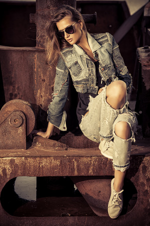 urban fashion: Stunning young woman in jeans clothes posing over urban background. Denim style. Fashion shot.