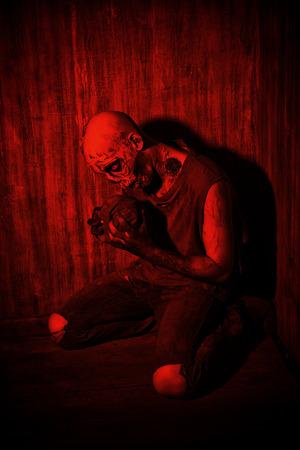 frightening: Frightening bloody zombie man in blood-red light. Halloween. Stock Photo