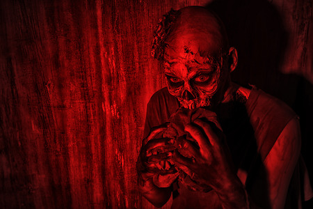 Frightening bloody zombie man in blood-red light. Halloween. Stock Photo